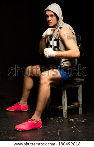 Young mean looking boxer waiting for a fight sitting on a stool with bandaged hands and his gloves hanging around his neck glaring at the camera - stock photo