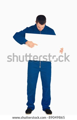Young mechanic in boiler suit pointing on banner in his hands against a white background - stock photo