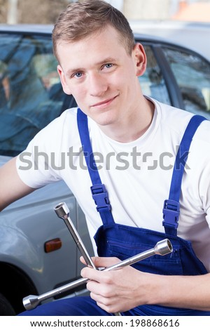 Young mechanic in uniform holding a tool