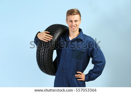 Young mechanic in uniform with tire on blue background