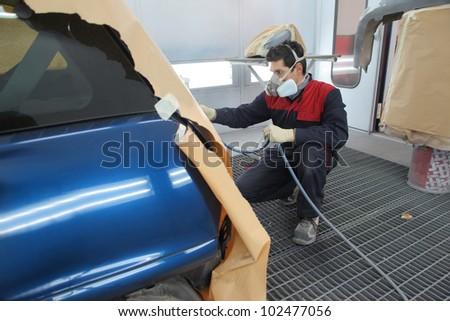 Young mechanic varnishing a car - stock photo