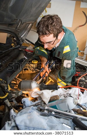 Young mechanic working on a car engine. - stock photo