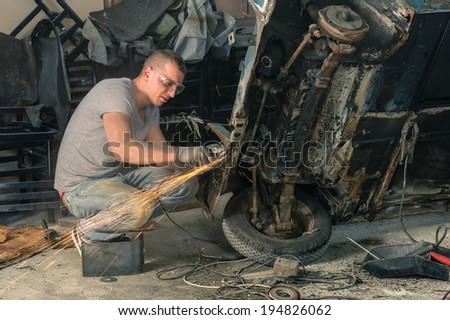 Young mechanical worker repairing an old vintage car body in messy garage - stock photo