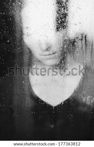 young melancholy and sad woman portrait  behind the window in the rain with rain drops on it - stock photo