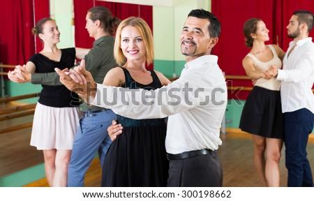 young men and women enjoying of tango in class - stock photo