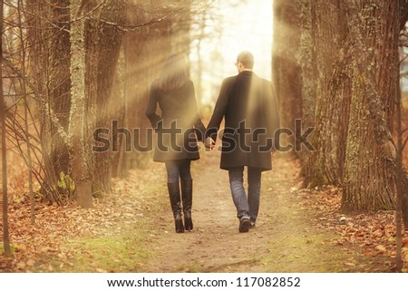 young men and women leaving the path in the park - stock photo