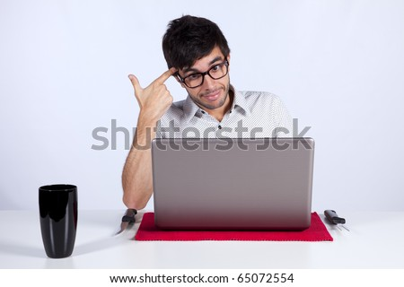 Young men at dinner table eating technology with a suicide gesture while working with his laptop - stock photo