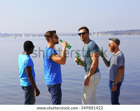 Young men drinking beer on the riverside - stock photo