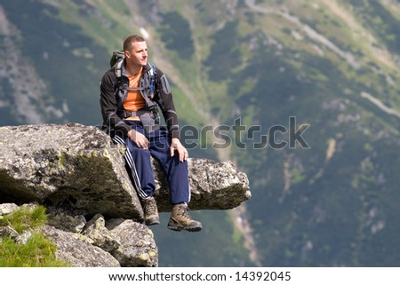 Young men is relaxing on the edge of precipice in Tatra Mountains