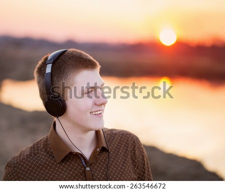 young men listening to music with headphones against outdoor - stock photo
