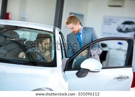 young men looking with car dealer at car in dealership - stock photo