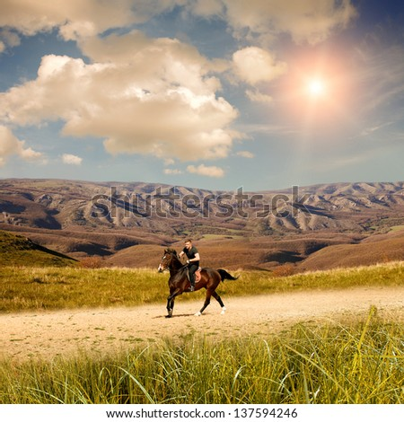Young men on the horse in mountians - stock photo