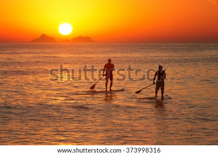 Young men paddle surfing at sunset in Ipanema beach, Rio de Janeiro.