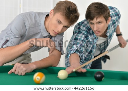 Young men playing billiards - stock photo