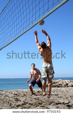 Young men playing volleyball on the beach - stock photo