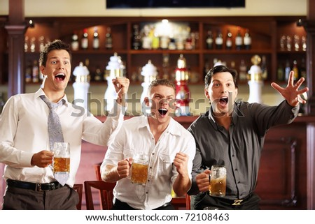 Young men rejoice the victory of his team in a bar