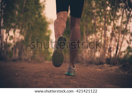 Young men running on a rural road during sunset - stock photo