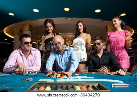 young men taking poker chips after winning - stock photo