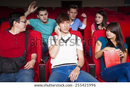 Young men talking on the phone while watching movie at the cinema - stock photo