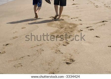 Young men walking on the beach - stock photo