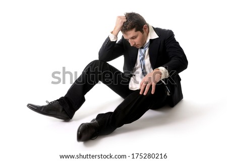 Young Messy Business Man worried and depressed sitting on the floor isolated on white background in stress because of financial crisis - stock photo