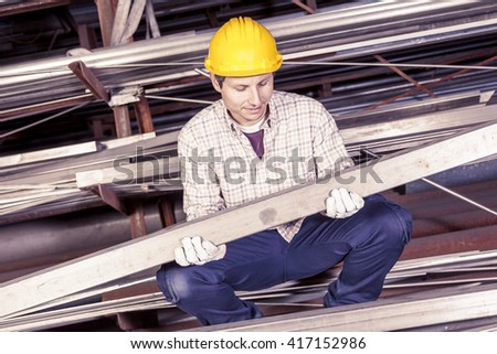 young metalworker controls some metal bars in steel mill - stock photo