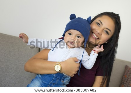 Young mexican mom with his baby boy - stock photo