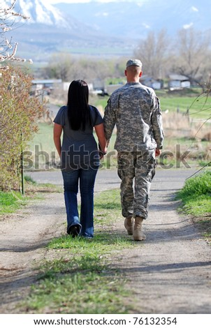 Young military couple walking down a country lane holding hands. - stock photo