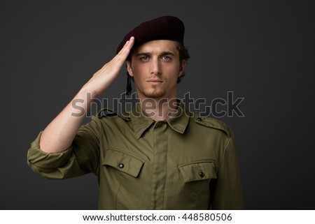 young military with red beret and green uniform on gray background, salute