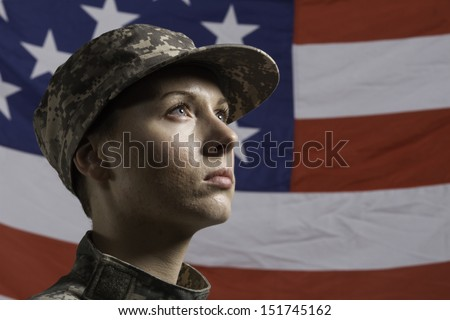 Young military woman pictured in front of US flag, horizontal - stock photo