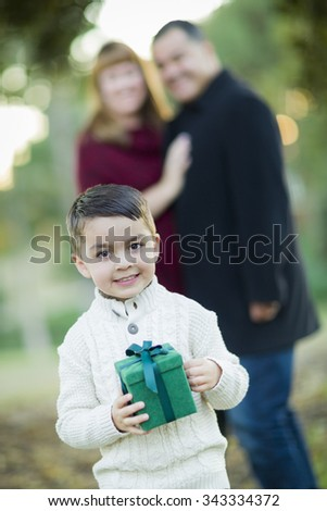 Young Mixed Race Boy Holding Gift In Front with Parents Behind. - stock photo