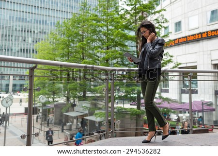 Young mixed race businesswoman portrait outdoors in Canary Wharf area in London walking with tablet.