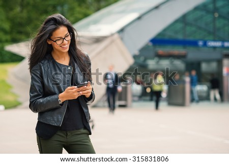 Young mixed race businesswoman portrait outdoors in Canary Wharf area in London with modern building as background while using smartphone. Filtered image. - stock photo