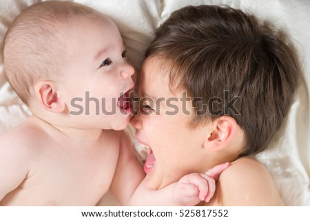 Young Mixed Race Chinese and Caucasian Baby Brothers Having Fun Laying In Bed.