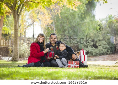 Young Mixed Race Family Enjoying Christmas Gifts in the Park Together. - stock photo
