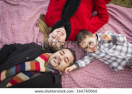 Young Mixed Race Family in Winter Clothing Laying on Their Backs on Picnic Blanket in the Park Together. - stock photo