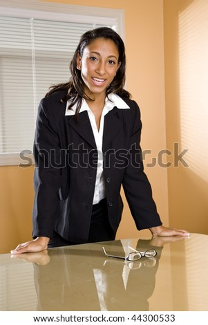Young mixed-race Hispanic African-American female office worker standing in boardroom - stock photo