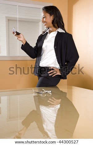 Young mixed-race Hispanic African-American woman in office boardroom texting on mobile phone - stock photo