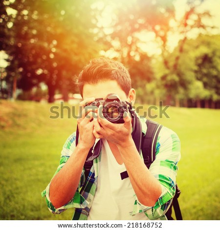 Young mixed race male photographer in park on sunny summer day using digital camera. Square image. Instagram filter look. - stock photo