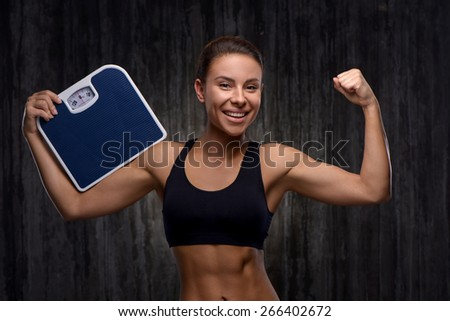Young mixed race sporty woman wearing black tracksuit for training. She cheerfully smiling, demonstrating biceps and holding weighs. Fitness and healthcare concept - stock photo