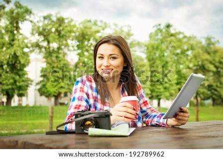 Young mixed race teenage tourist woman in park on summer day with tablet, map and camera drinking coffee. Traveling concept. - stock photo