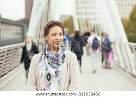 Young mixed race woman walking on a bridge in London. She is smiling and looking away from camera. There are some blurred persons on background. Tourism and lifestyle concepts. - stock photo