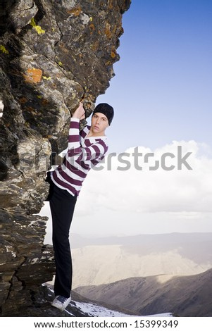 Young model climbing a small cliff at high altitude in casual clothes. - stock photo