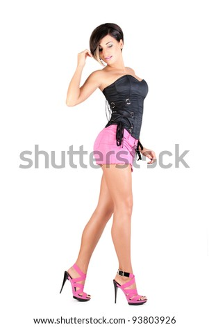 young model in pink mini skirt and black corset posing, isolated on white - stock photo