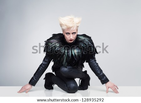 young model with crazy hair and leather clothes posing and looking at camera on a white platform with grey background - stock photo
