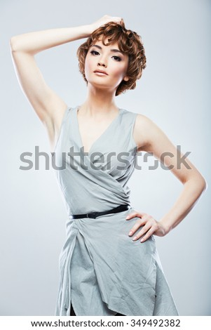 Young model with short curly hair posing in fashion style at studio. Beautiful young woman snapshot.