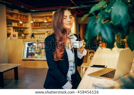 young modern business woman has a coffee break while working with a laptop computer. attractive girl drinking coffee in a modern coffee shop and using laptop and smart-phone. - stock photo