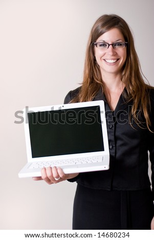 Young modern business woman holding out a laptop computer. Personal text or images can be inserted onto the laptop portion.