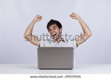 young modern businessman excited with his success with his laptop computer - stock photo