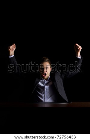 Young modern businessman in dark suit sitting at office desk and raising hands celebrating business success, low-key image isolated on black background. - stock photo